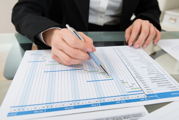Close-up Of Businesswoman With Pen Working On Gantt Chart At Desk
